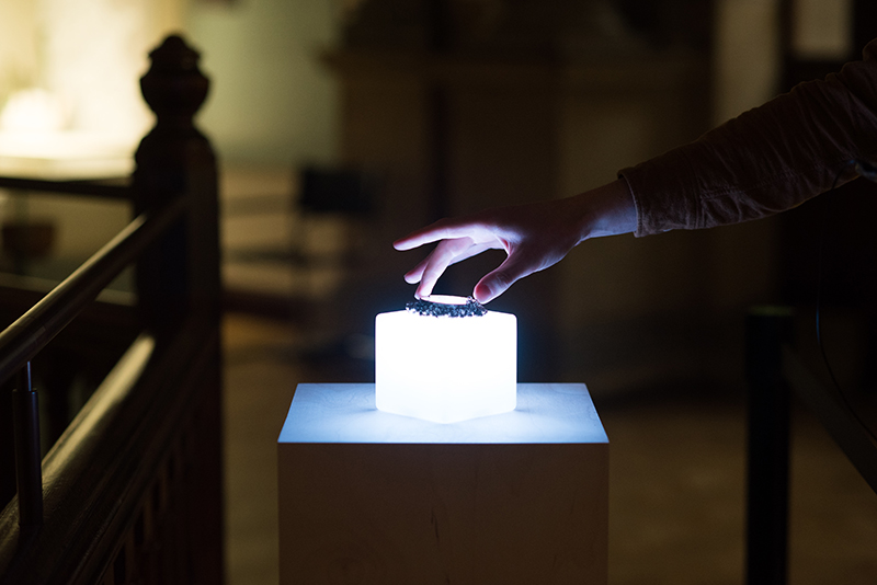 Photograph of a hand reaching out to touch an artefact on an illuminated cube.