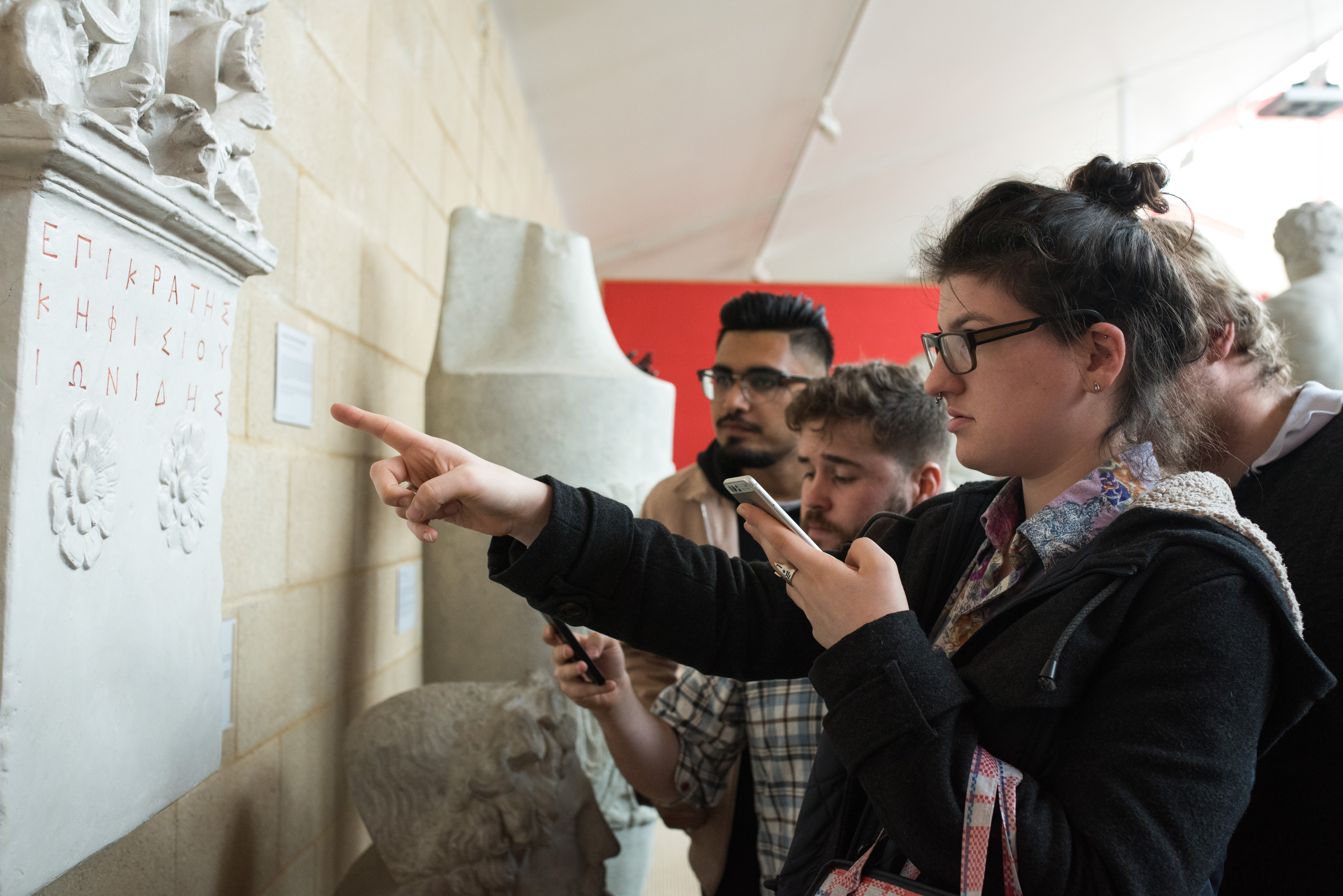 Four players holding their phones look closely at an inscription on the wall of the Museum of Classical Archaeology