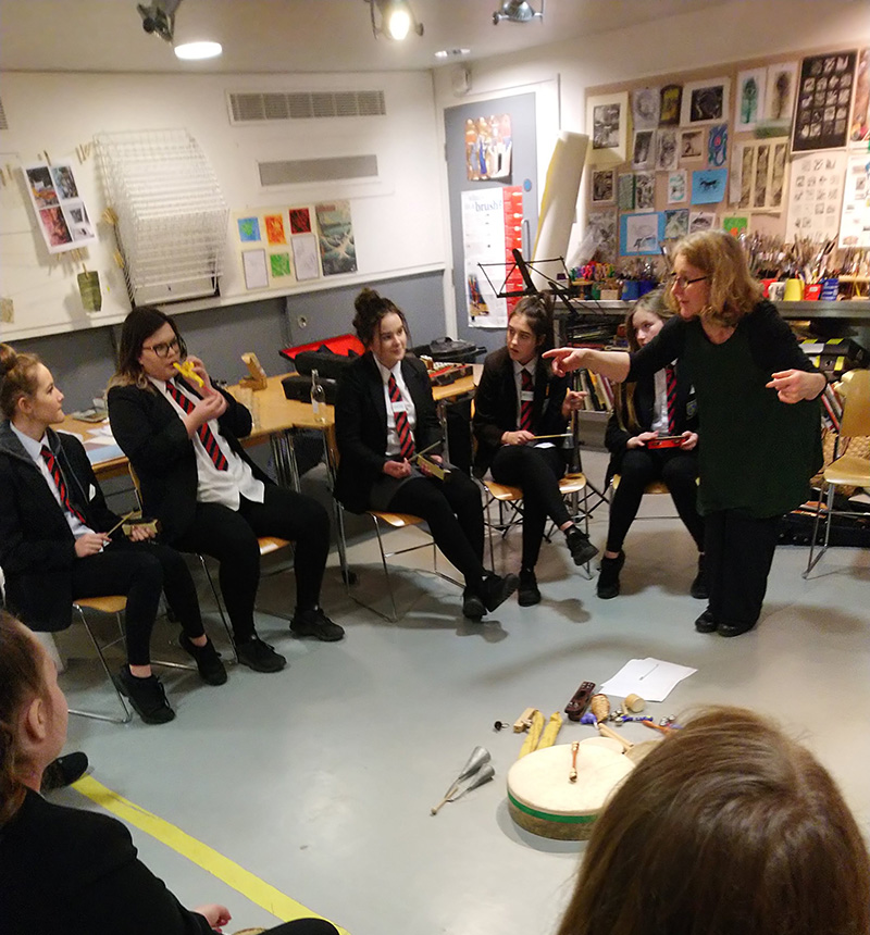 Students sit in a circle and experiment with different musical instruments, including recorders and drums