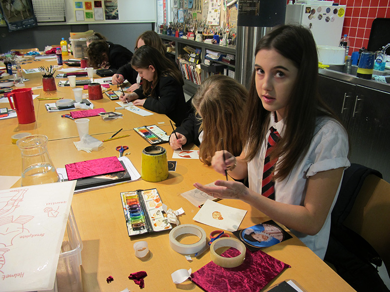 Students at a workbench in the Museum's studio use paints and craft materials to make their portraits