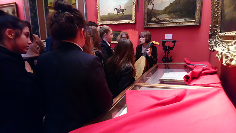 Students gather around a curator holding a lute
