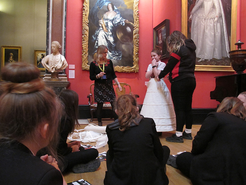 A student tries on a wide, white Elizabethan underskirt