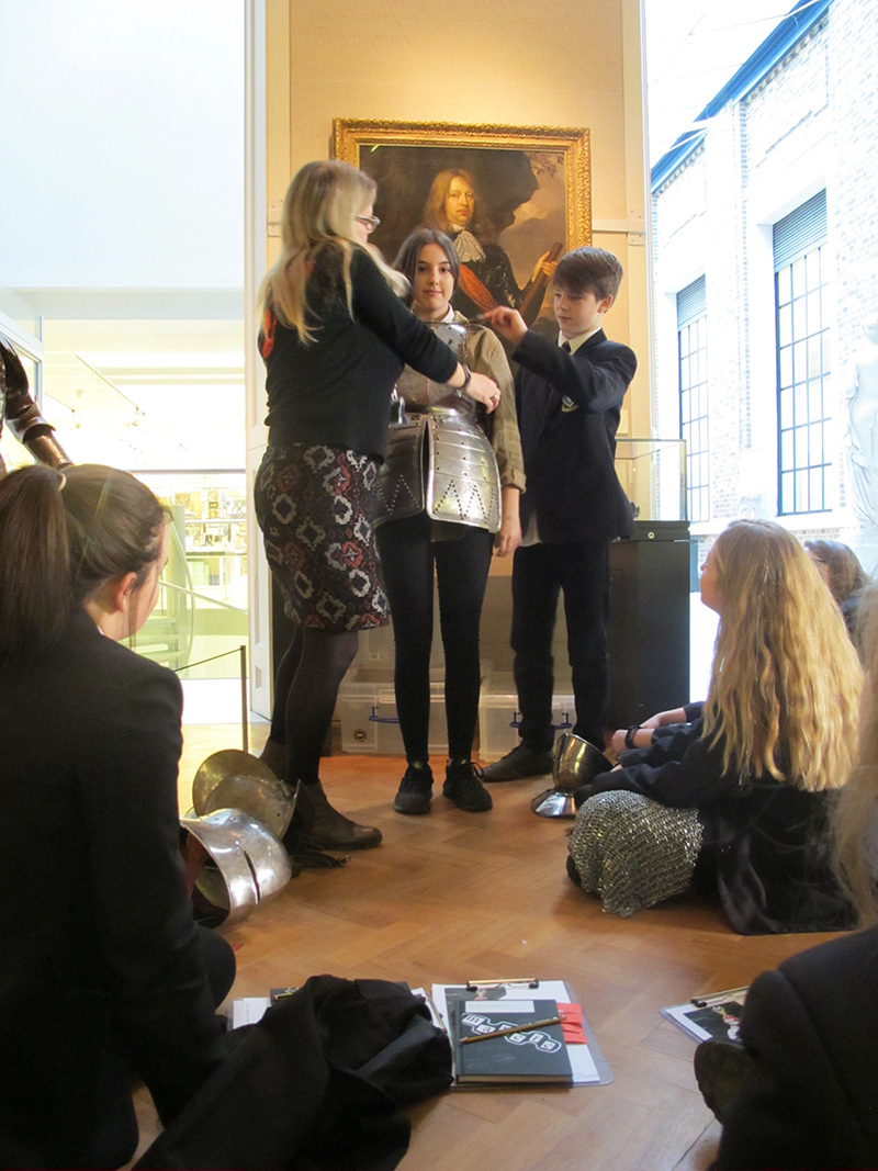 Secondary school students try on armour in the museum's Armoury