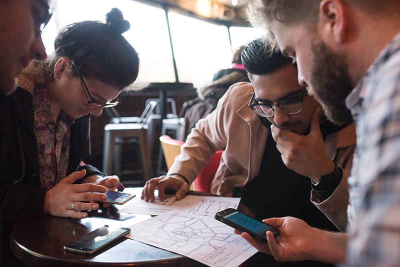 Players around a table look at a map to decide which museums to try first