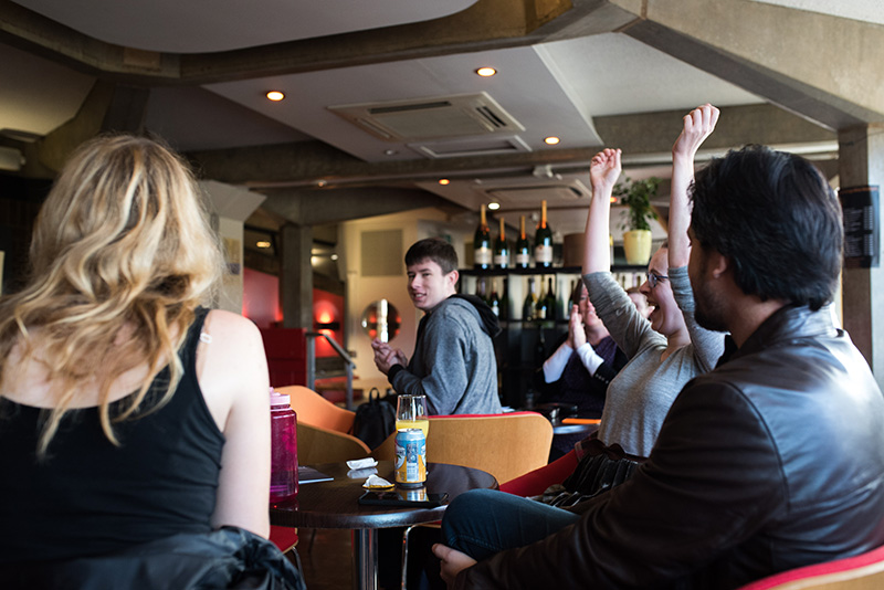 Players seated in a bar. One girl is smiling with her hands in the air in a celebratory gesture