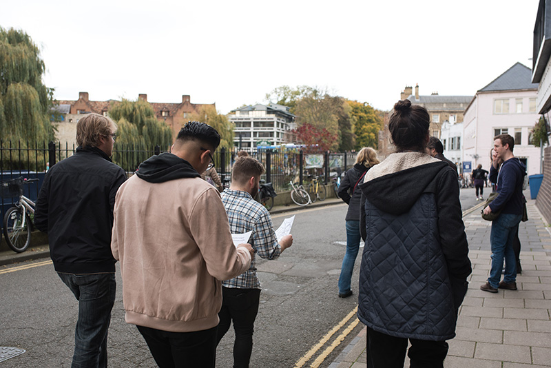 Group of four players shown from the back as they walk down a lane by the river, looking at their maps
