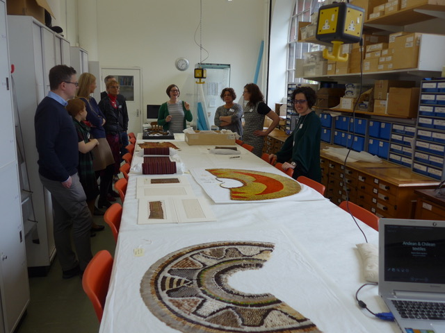 A group of researchers discuss textiles objects in the Museum workroom