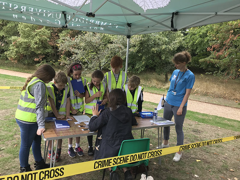 """A cluster of children and a museum educator gather around a table under an awning on a lawn in the Botanic Garden. Yellow plastic tape extends across the picture saying """"Crime Scene Do Not Enter"""""""