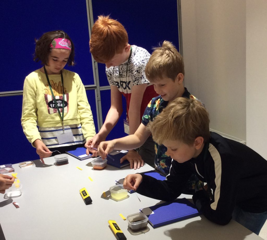 Four children use litmus papers to test the pH of different coloured soil samples in small plastic tubs