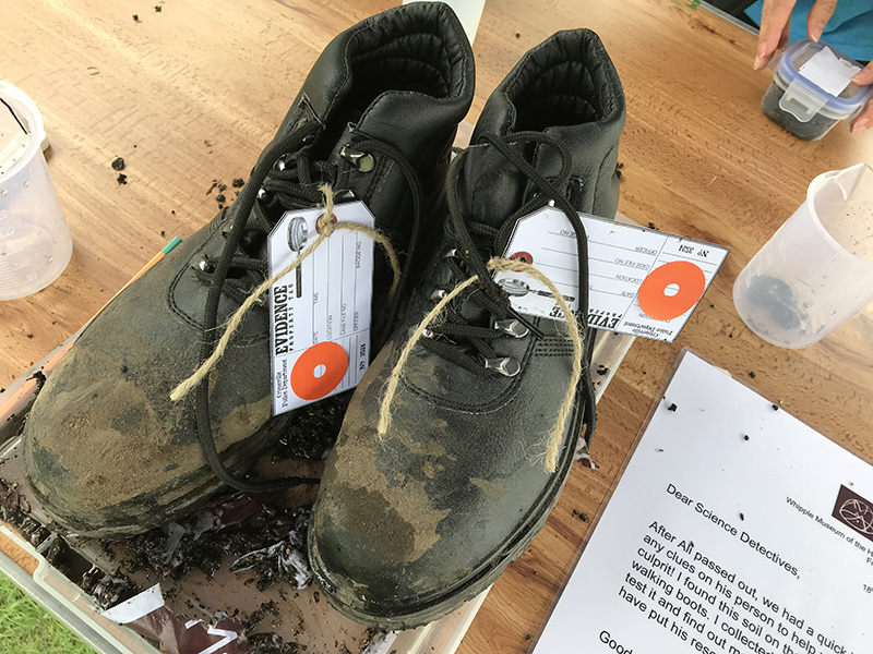 """A pair of muddy black boots, labelled as """"Evidence"""""""