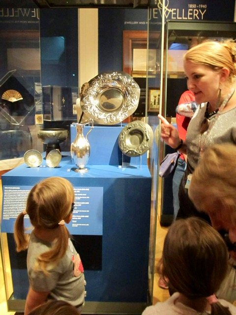 Children explore the exhibition with museum educator Nicola. They look up at a display case containing large silver plates and jugs.