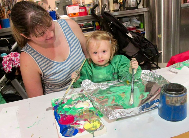 A baby wearing a green overall sits on her mum's lap, painting green paint on foil.