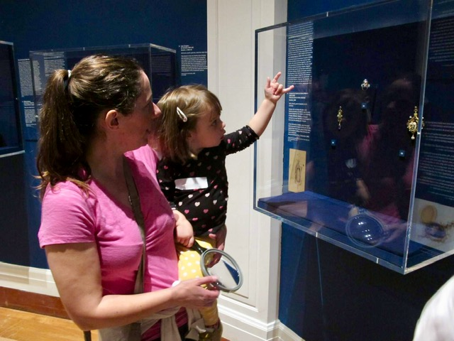 A mum and baby explore a case in the Jewellery exhibition. The case has a dark blue background with gold jewellery displayed inside.