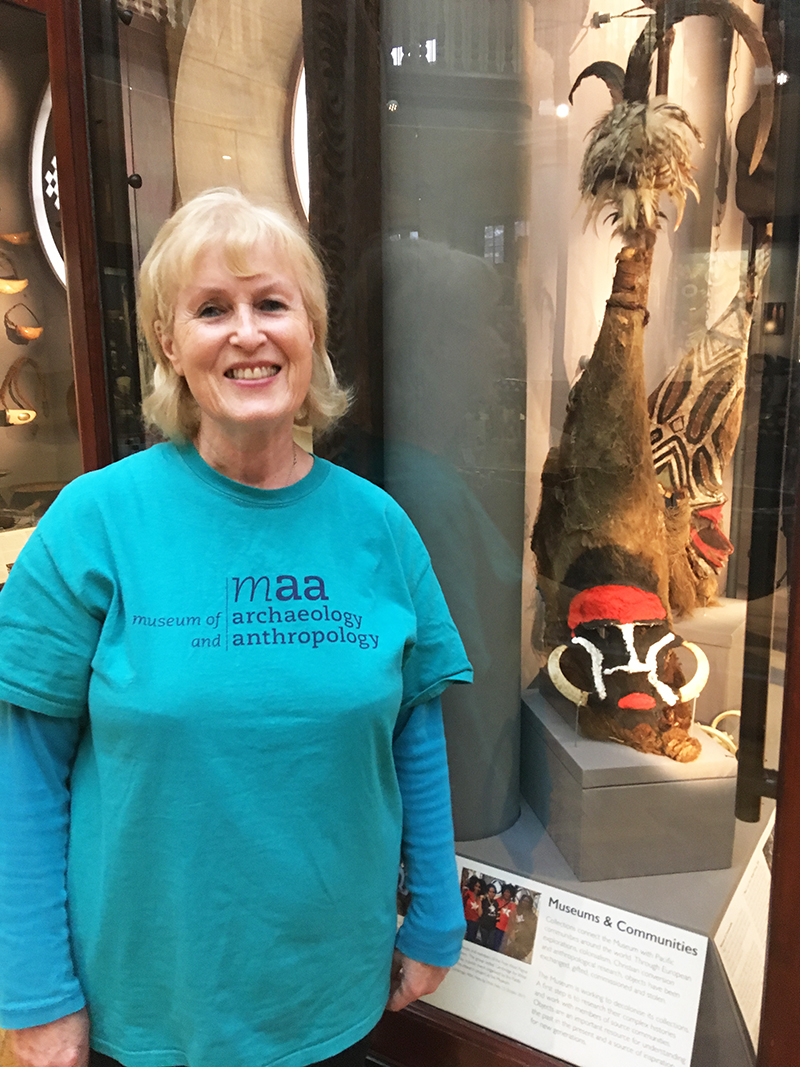 Gloria, a fair-haired lady dressed in a blue MAA tshirt, stands in front of one of the Pacific Islands display cases