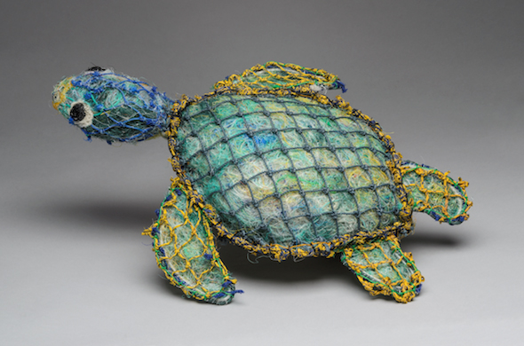 A sculpture of a turtle made from blue plastic fibres wrapped in recycled yellow and blue netting, displayed against a grey background as if swimming towards the edge of the frame.