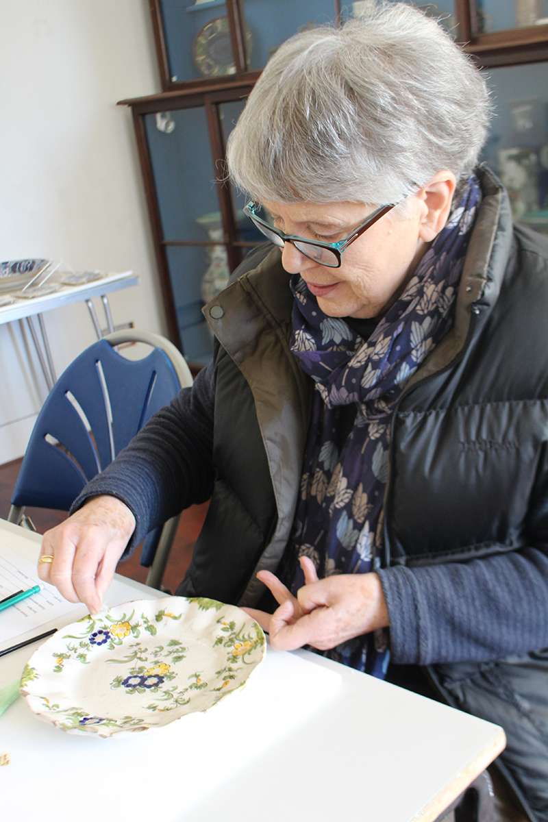 A volunteer wet-cleaning a dish with a delicate floral pattern with a damp swab