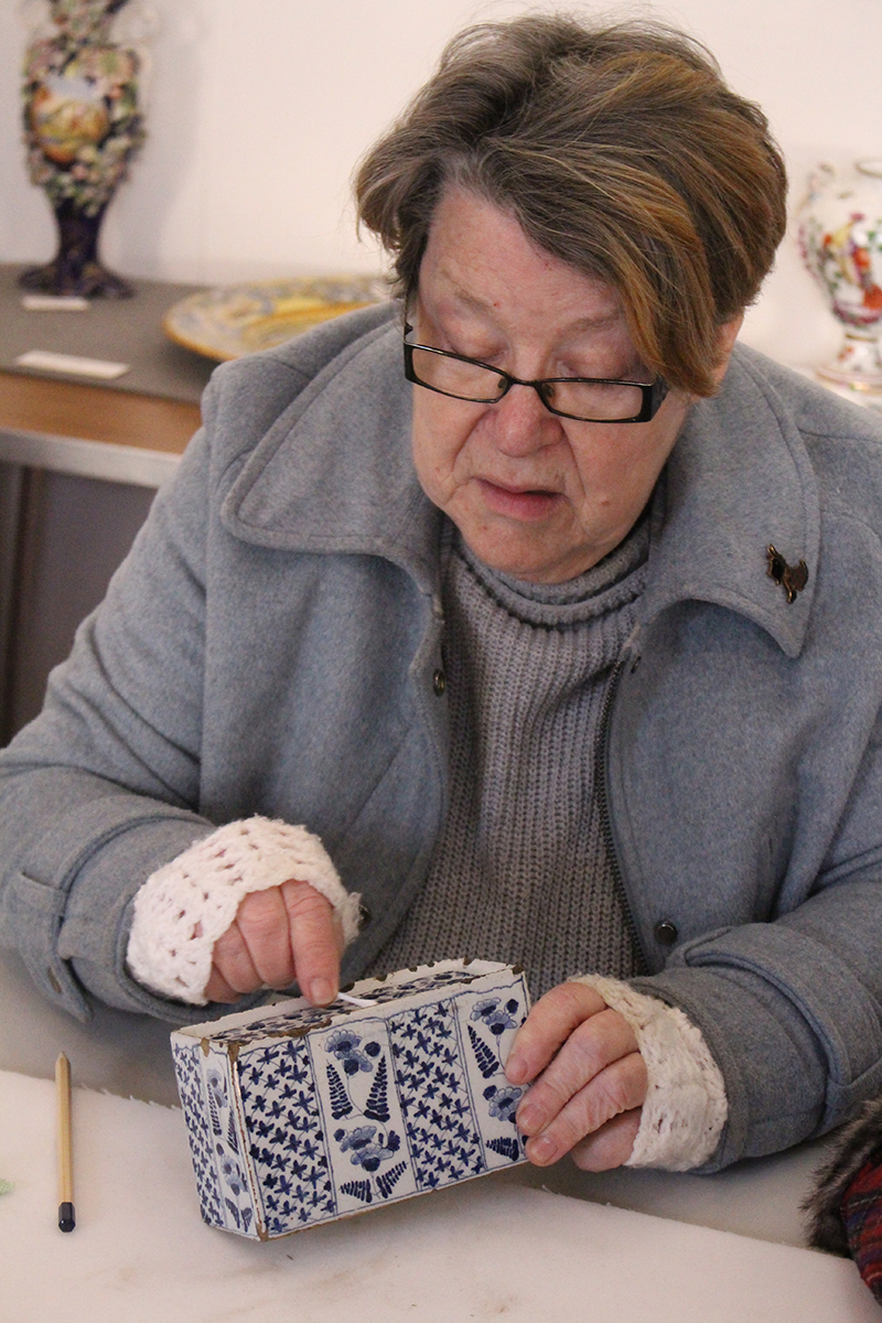 A volunteer cleaning a blue and white Delftware flower brick with a cotton bud. The brick is slightly chipped along its edges.