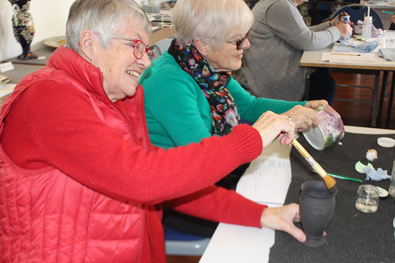 A volunteer dry-cleaning a black basalt vase with a brush whilst her neighbour wet-cleans with a damp swab