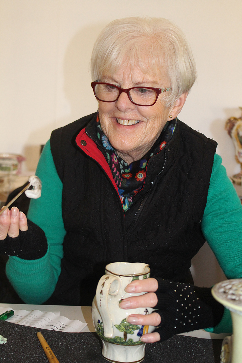 A smiling volunteer steadies a small vase in one hand and holds up a dirty swab in the other