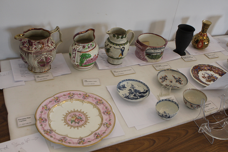 A spread of ceramic plates, jugs, small bowls, laid out on a table with their condition reports tucked beneath them