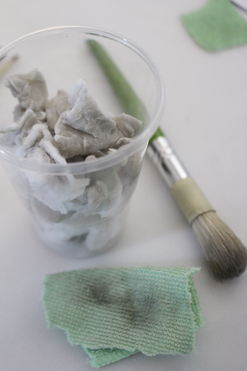 A plastic cup full of dirty cotton swabs, a dirty scrap of microfibre cloth, and a brush