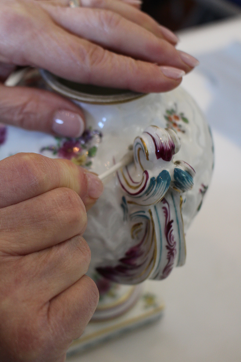 A close up of two hands, one stabilising a white pot with elegant handle, the other gently cleaning with a cotton bud