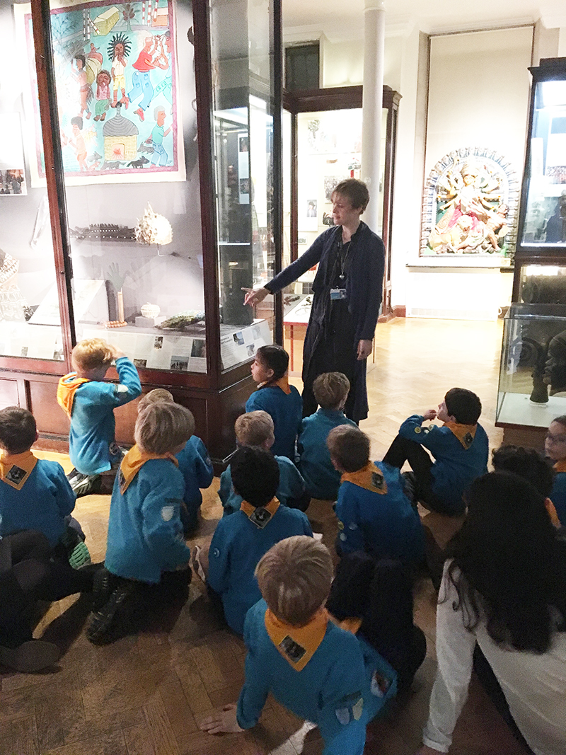A class of primary school pupils listen to Jenny as she teaches in the gallery