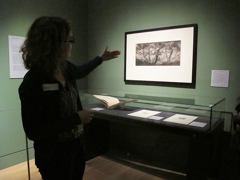 Museum educator Kate gestures to a drawing in a darkened gallery
