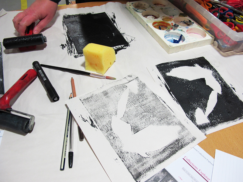 A shot of a worktable in the stdio, with sponges, brushes, and a black and white print in progress