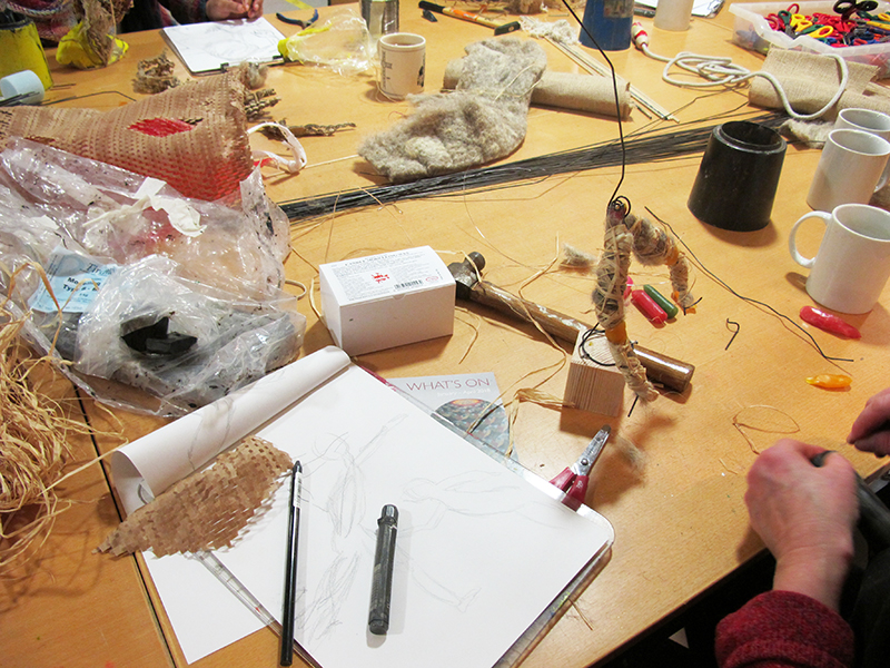 A studio table covered with craft materials, including a model work in progress
