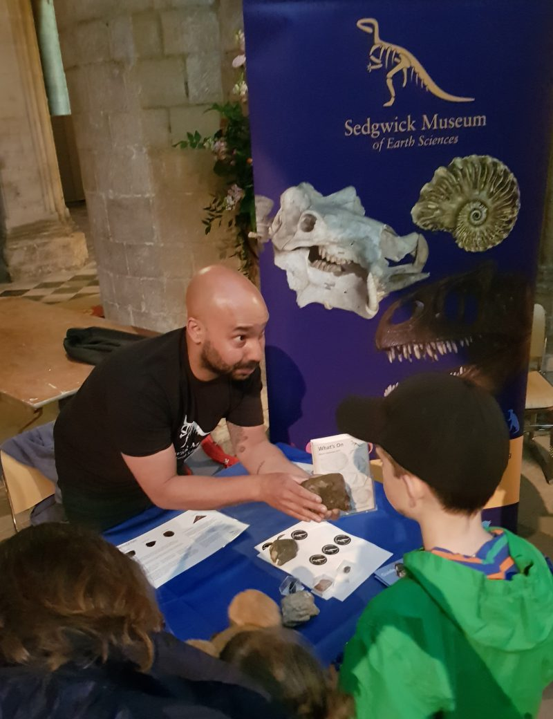 children looking at rock specimens at the Sedgwick Museum's stall