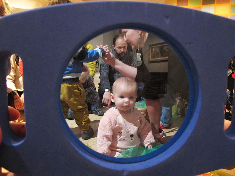 a baby peeps through a toy