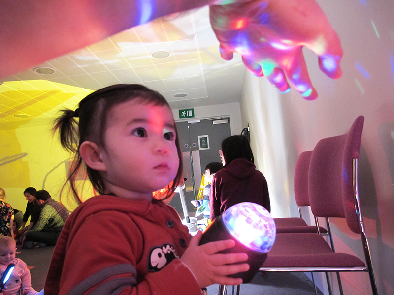 a toddler explores the lights and shapes created by a disco ball
