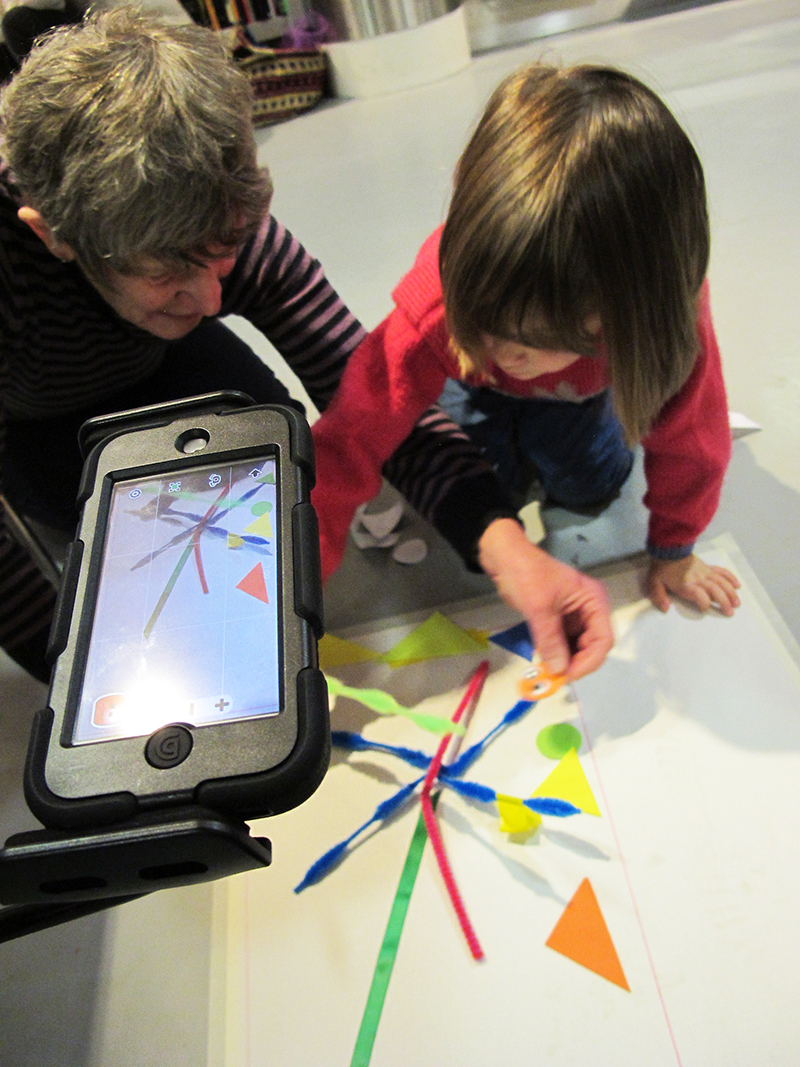 An adult and child work together with colourful shapes to make an animation, using an ipod