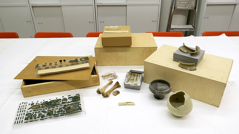 a selection of small finds and boxes laid out on a work bench