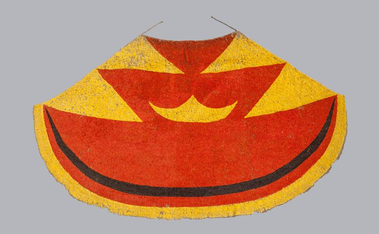 A bright red, yellow and black Hawaiian feather cloak
