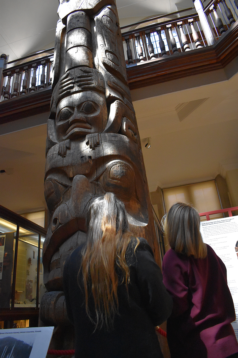 Two students looking at a totem pole in the Museum