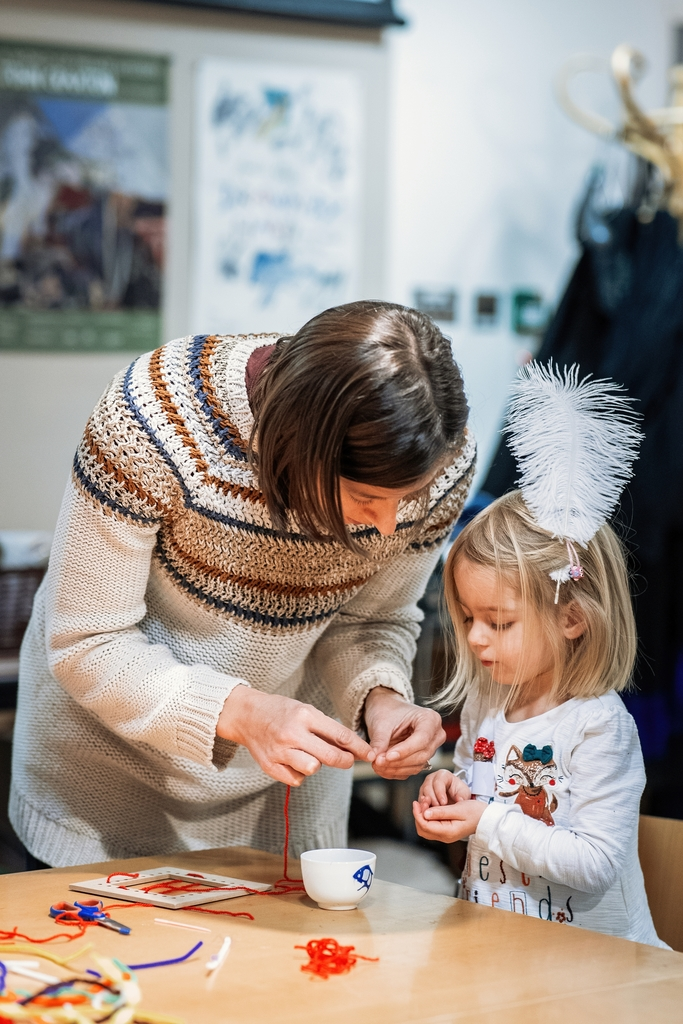 Adult and child creating art with textile materials in the Museum