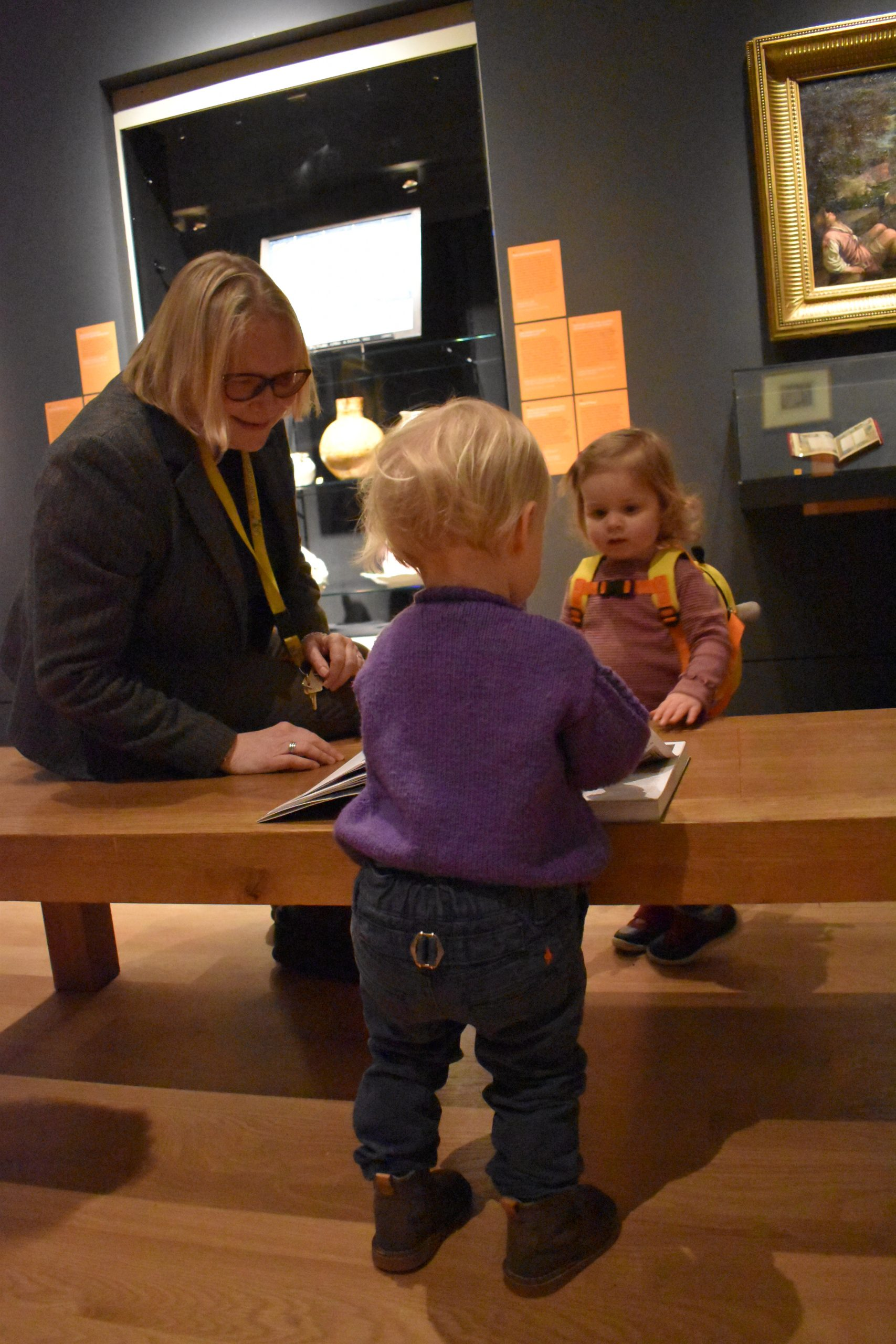 Young visitors sharing Feast and Fast Exhibition catalogue with curator, Vicky Avery