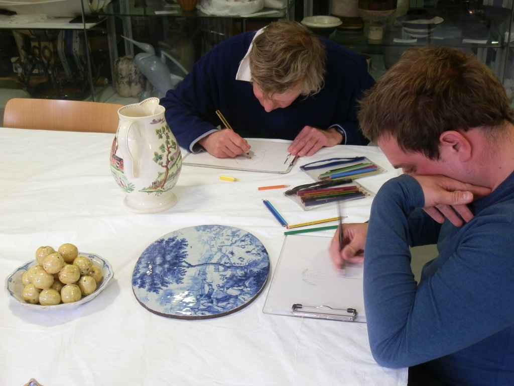 Peter drawing the farmyard jug and Frank drawing the Delftware wall-plaque of coney catching
