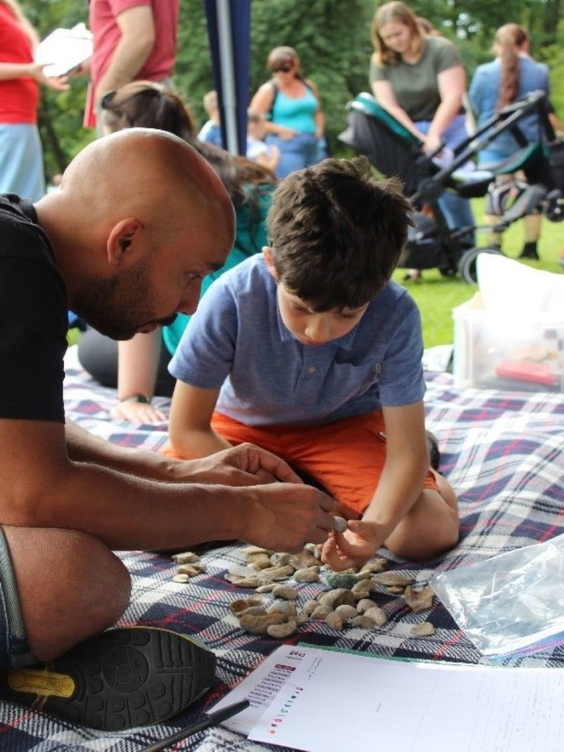 Rob looking closely at fossils with ChYpPSp participant