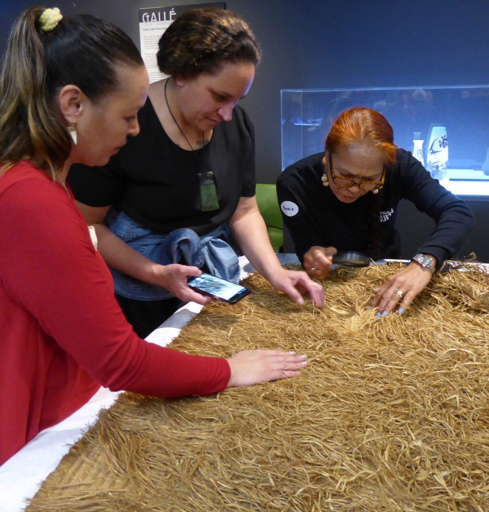 Three women examining a Māori cloak