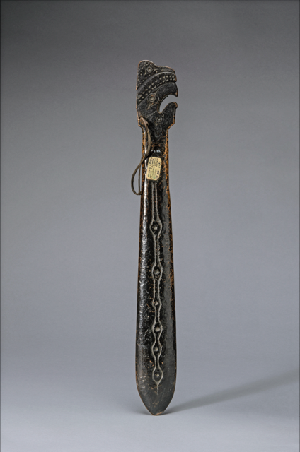 Bronze hand club with incised designs and bird-like head