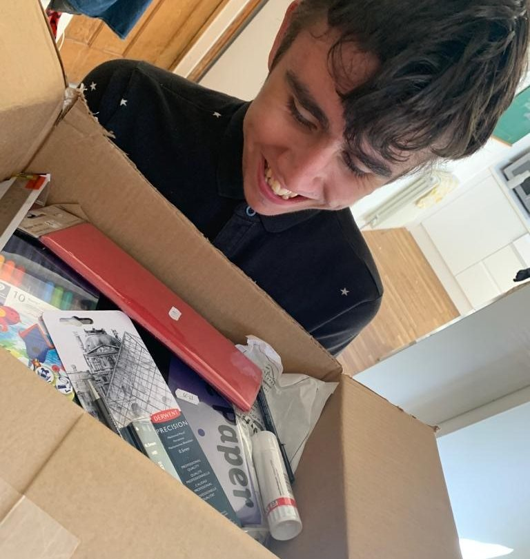 An arts pioneer receiving their box of art supplies