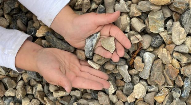 A child holding gravel