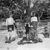 Picnic on the beach with (left to right) Haddon (seated), Pasi, Ray, probably Koriba, Mrs Canoe, unknown youth, and Poi Pasi (squatting). 14 May 1888.