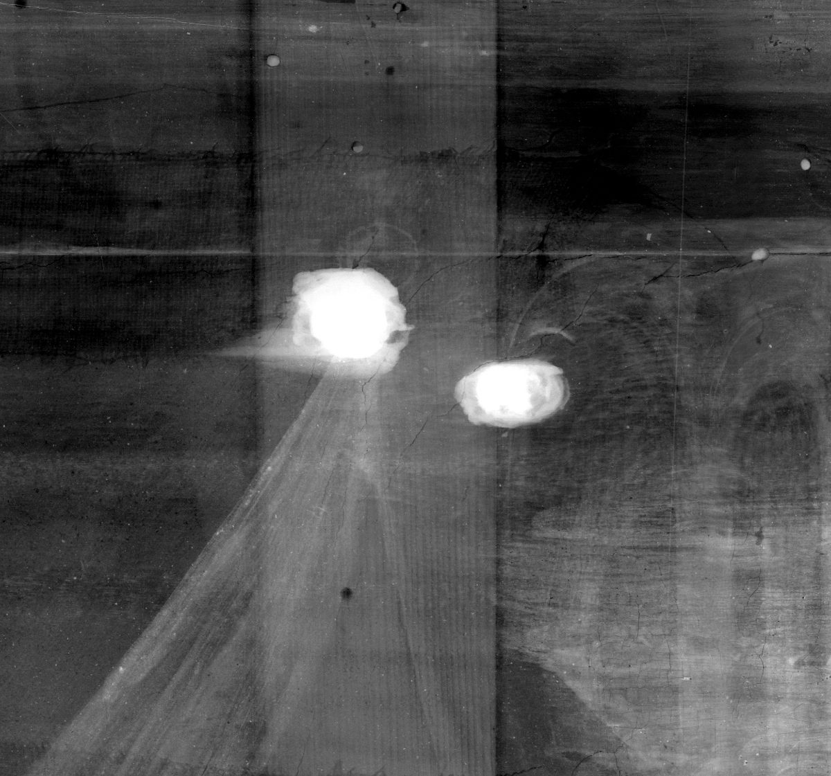 Section of x-ray of Cupid & Psyche showing some filler. The filler is in two circles and appears white against the dark wood and painting.