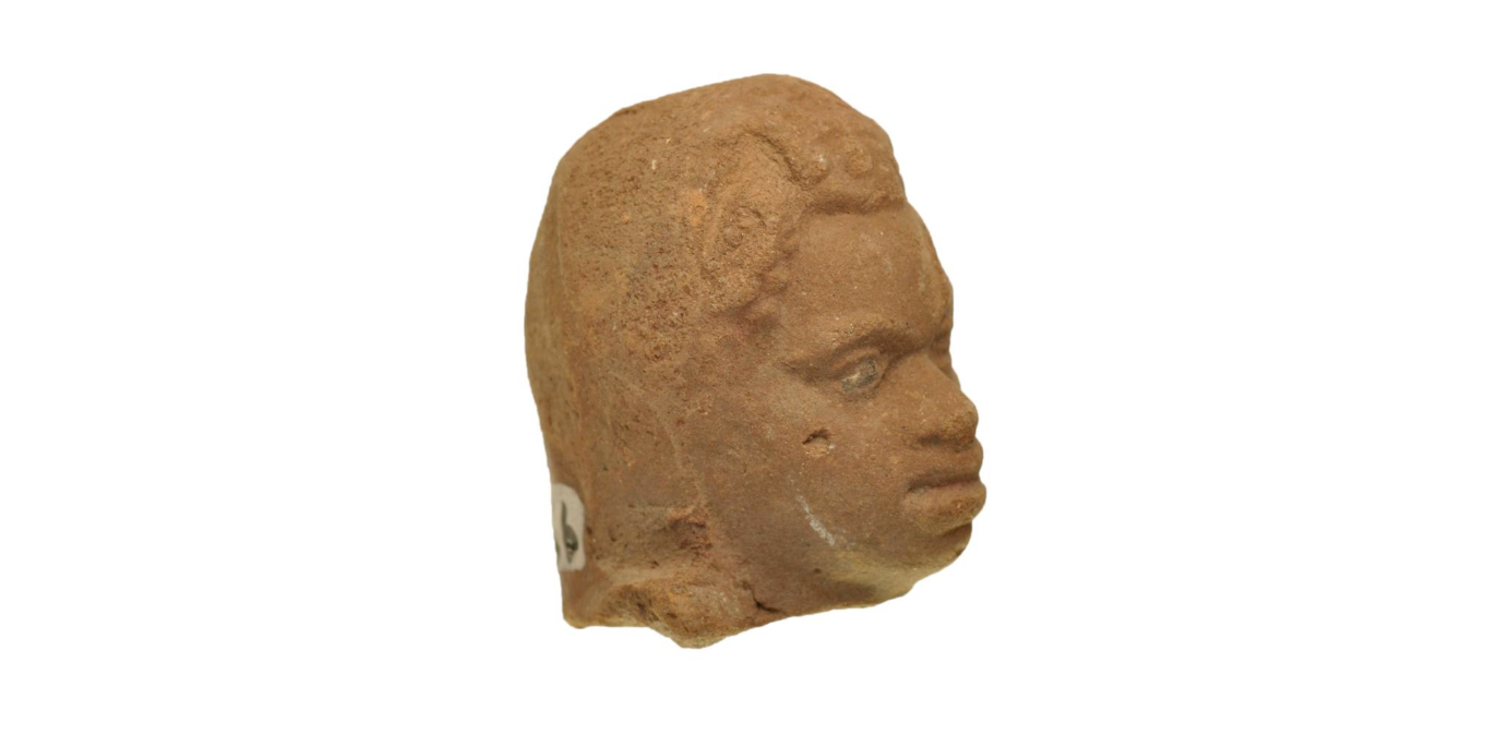 side view of terracotta figurine head, looking right