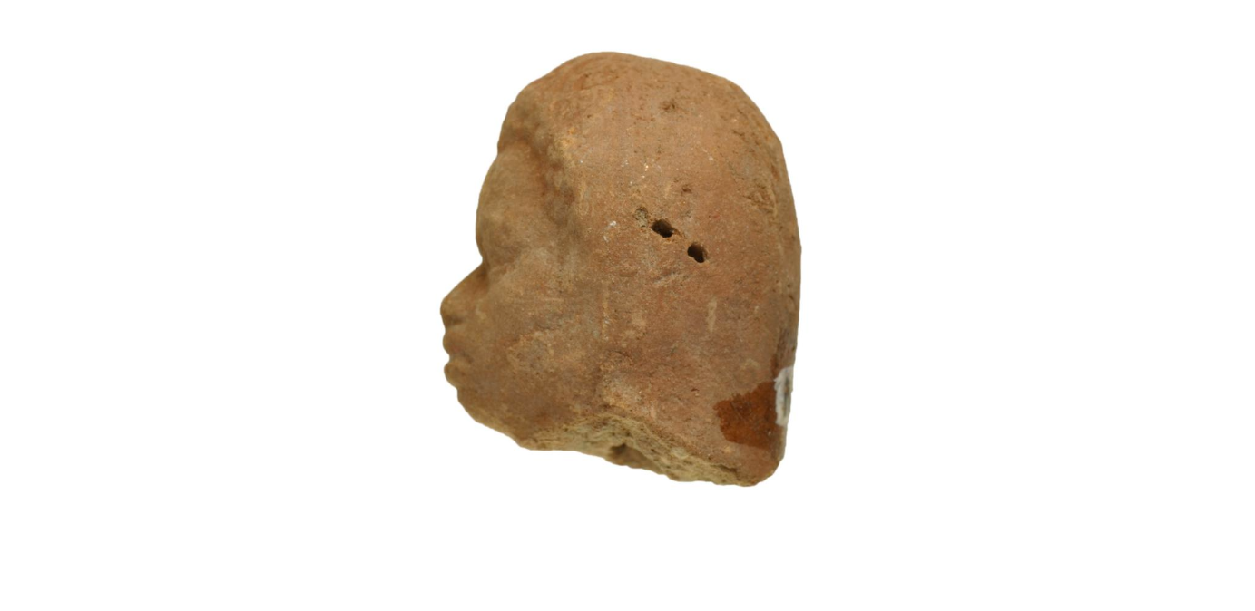 Side view of terracotta figurine head, looking left