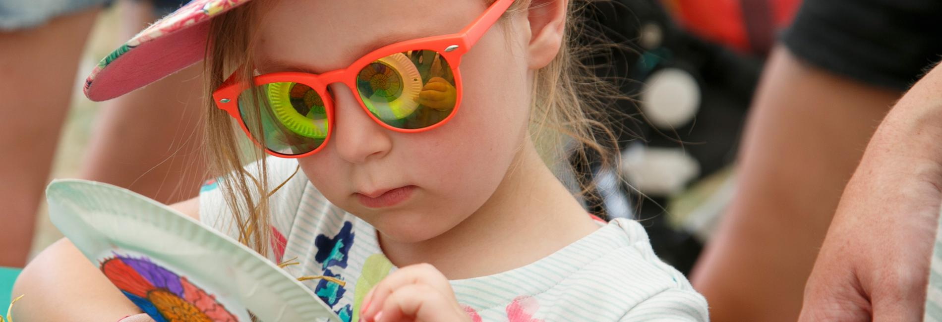 girl with ammonite pattern reflecting in her sunglasses